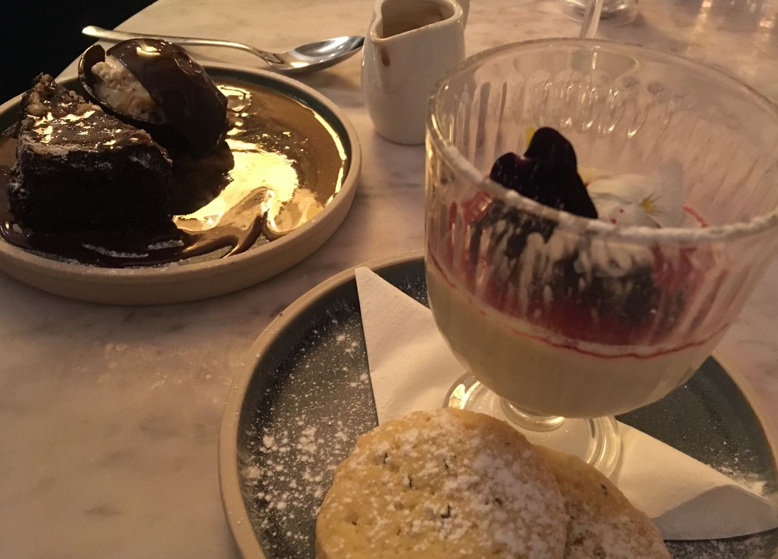 Lemon posset with mixed berry compote and chocolate dome with hazelnut torte at Aqua.